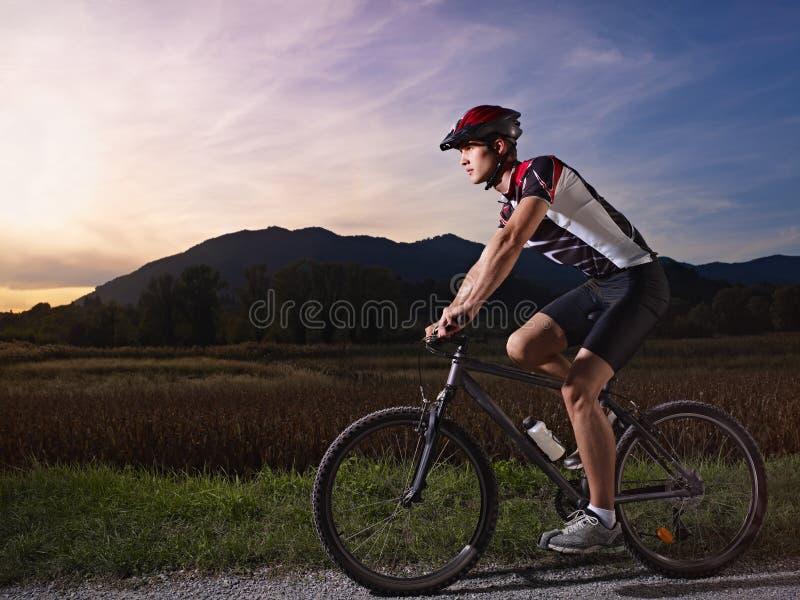 Young man training on mountain bike at sunset stock photo