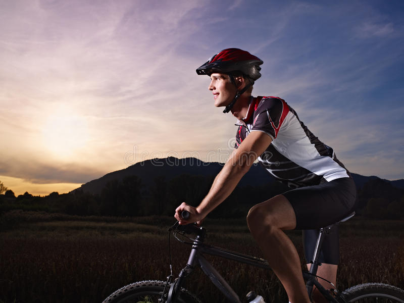 Young man training on mountain bike at sunset royalty free stock image