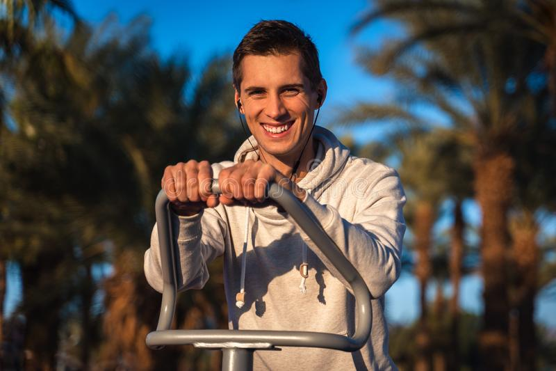 Young man training in a outdoor gym stock images