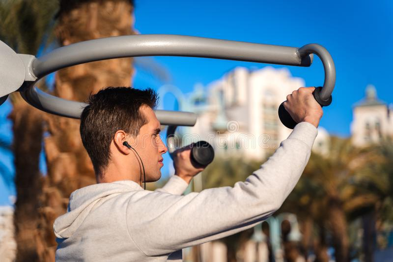 Young man training in a outdoor gym stock photo