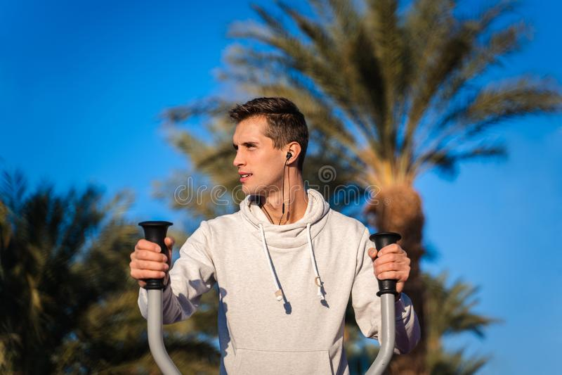 Young man training in a outdoor gym royalty free stock photos