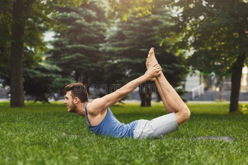 Young man training yoga in bow pose outdoors stock image