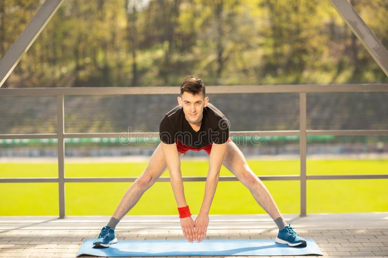 Young man training yoga outdoors. Sporty guy makes stretching exercise on a blue yoga mat, on the sports ground stock photos