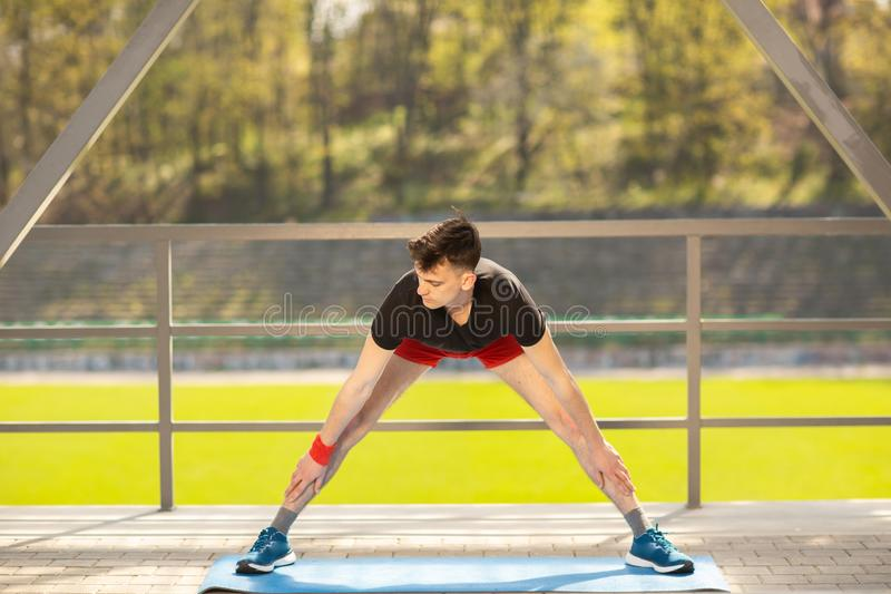 Young man training yoga outdoors. Sporty guy makes stretching exercise on a blue yoga mat, on the sports ground stock photo