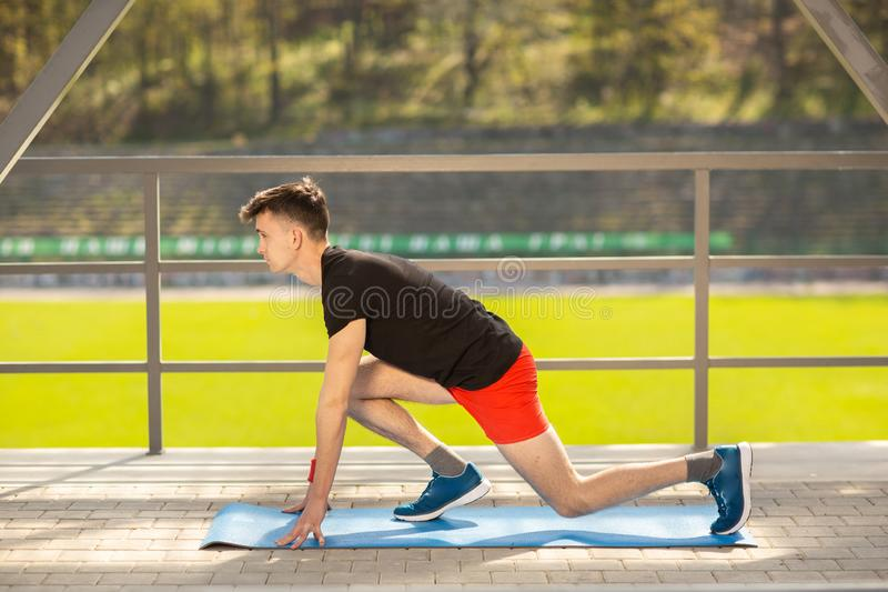 Young man training yoga outdoors. Sporty guy makes stretching exercise on a blue yoga mat, on the sports ground royalty free stock photography