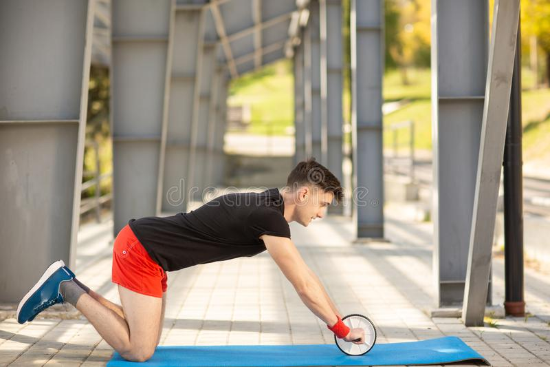 Young man training yoga outdoors. Sporty guy makes stretching exercise on a blue yoga mat, on the sports ground stock image
