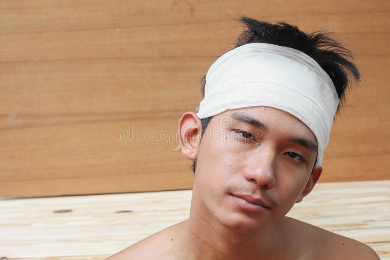 Young man with trauma of the head. by Medical bandage. Portrait show stock photography