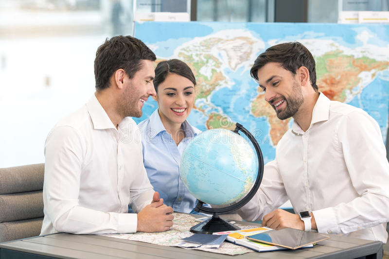 Young Man Travel Agent with Clients Concept royalty free stock image