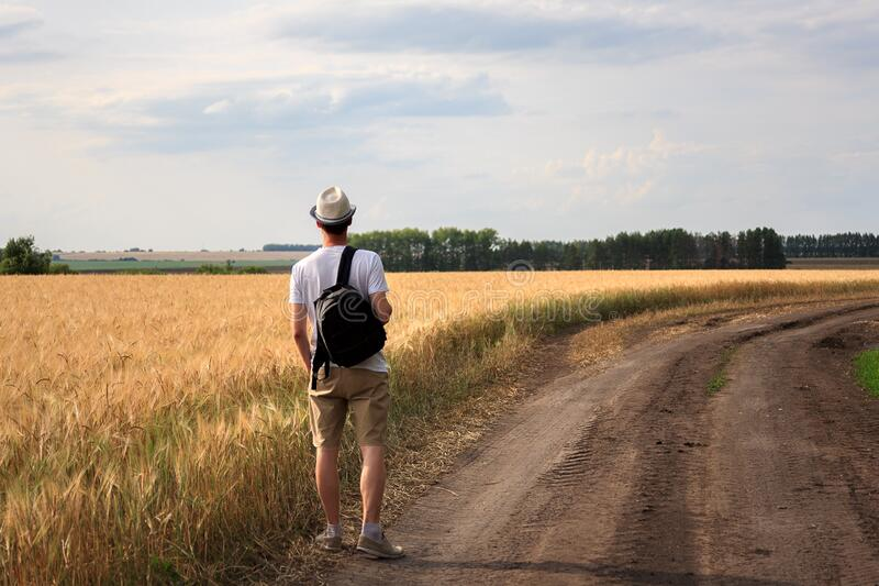 Young man traveler with backpack in hat stands in field at sunset and looks away, concept of freedom of choice, future, concept of. Travel and adventure royalty free stock photo