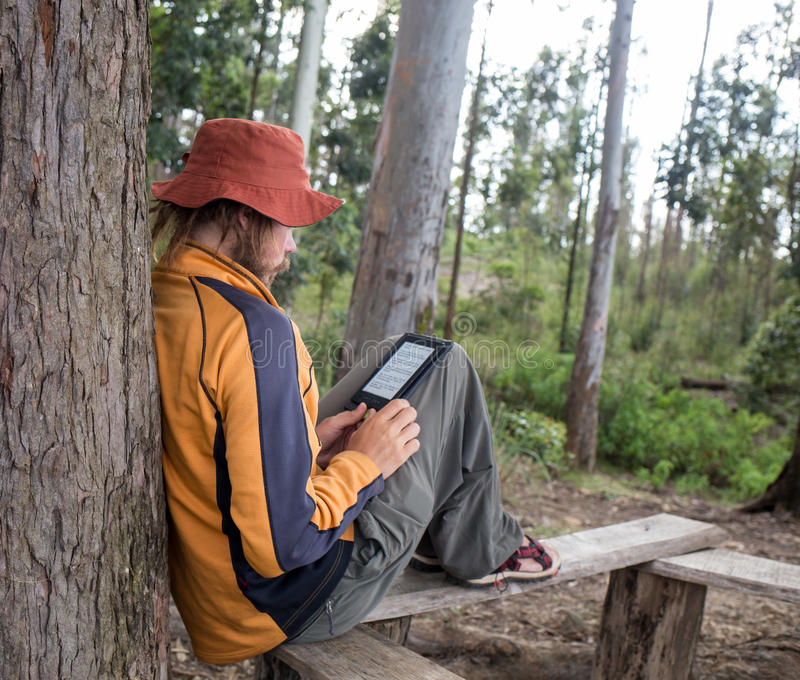 Young Man Traveler with backpack reading book stock photo