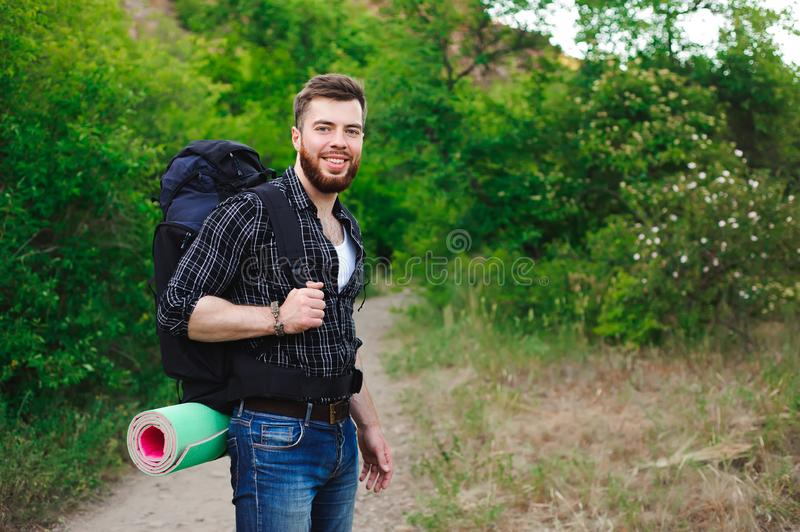 Young Man Traveler with backpack relaxing outdoor. Summer vacations and Lifestyle hiking concept. royalty free stock image