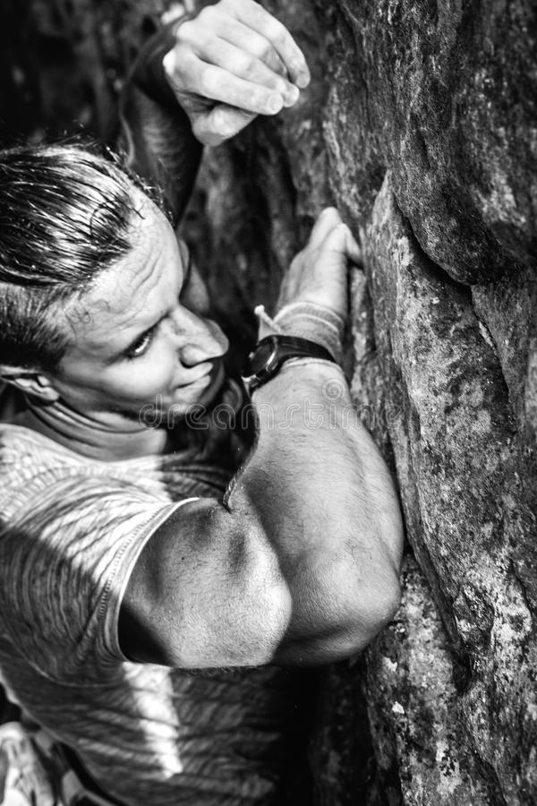 Young Man Traveler Climbing On Rock Wall. Achieving Goals Concept. A young man climbs up a cliff, close-up, arms a powder of magnesia. Positive personality royalty free stock photo