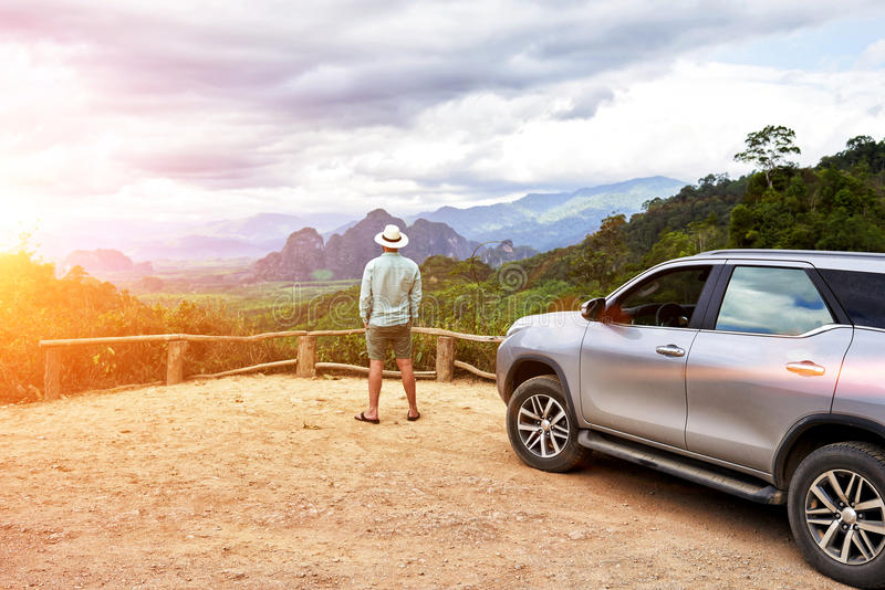 Young man traveler is enjoying gorgeous view during his road trip on suv in Thailand. Back view of a hipster guy is looking away, while is standing on a mountain royalty free stock photo
