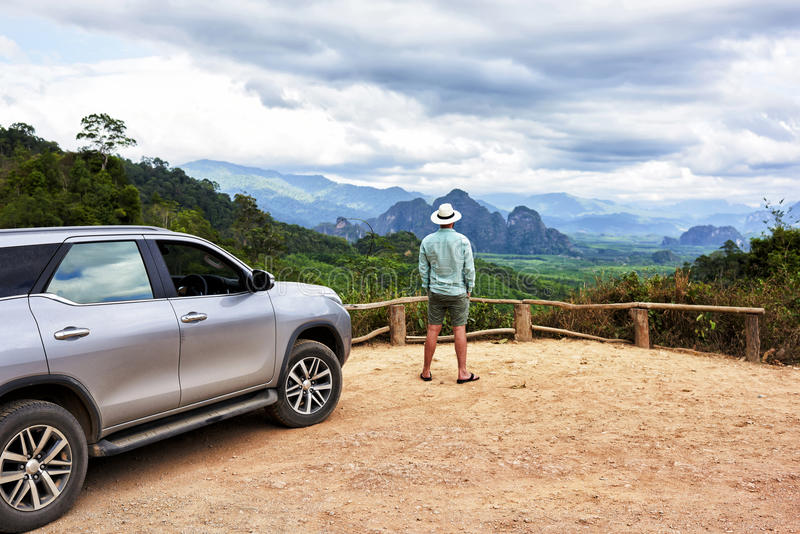Young man traveler is enjoying gorgeous view during his road trip on suv in Thailand. Back view of a hipster guy is looking away, while is standing on a mountain royalty free stock image