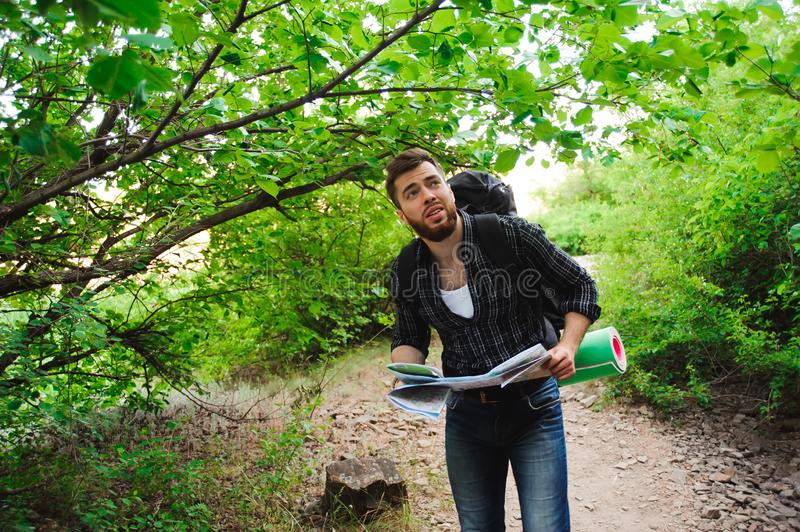Young Man Traveler with map backpack relaxing outdoor on background summer vacations and lifestyle hiking concept royalty free stock photography
