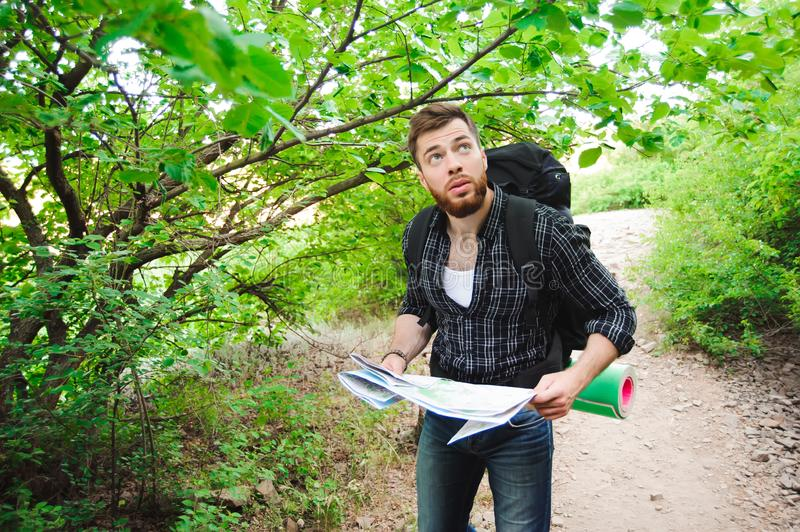 Young Man Traveler with map backpack relaxing outdoor royalty free stock image