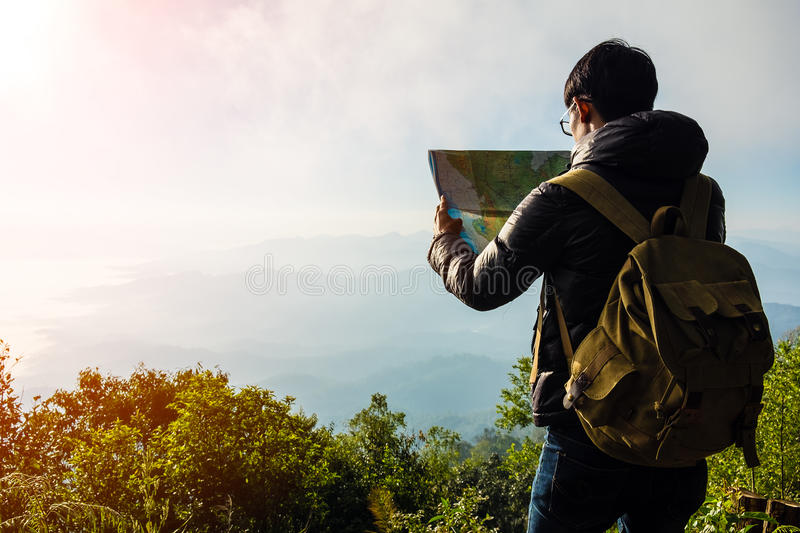 Young Man Traveler with map backpack relaxing outdoor stock photo