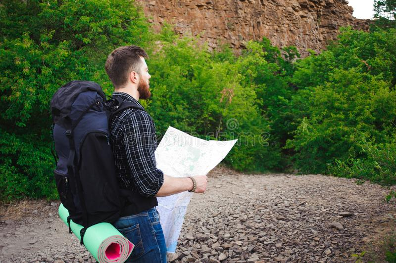Young Man Traveler with map backpack relaxing outdoor stock photography