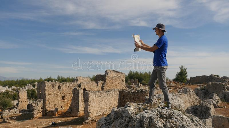 Young man traveler with map exploring ancient city. Young man tourist in panama hat with map exploring ancient city Lyrboton in Turkey royalty free stock photo