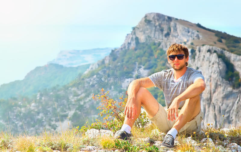 Young Man Traveler relaxing with Mountains on background stock images