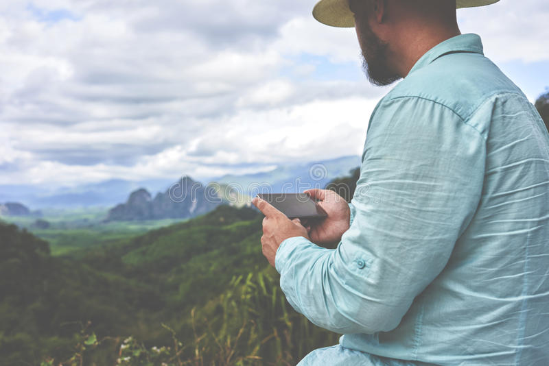 Young man traveler is waiting until the video is downloaded on cell telephone. Closeup of bearded hipster guy is holding mobile phone with copy space on the royalty free stock photos