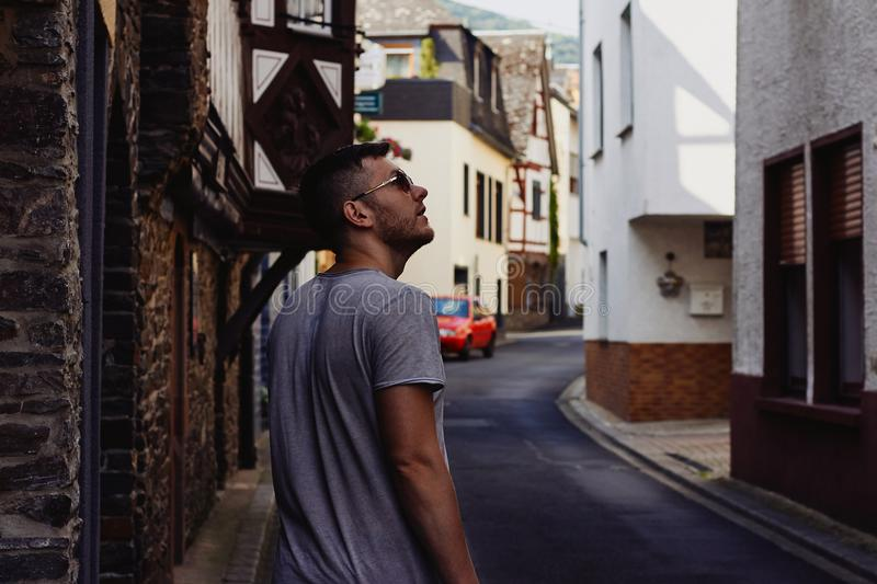 Young man traveler is walking along the narrow paved street with medieval houses stock photo