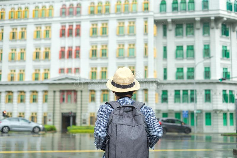Young man traveling with hat, Solo Asian traveler visit at rainbow colorful building in Clarke Quay, Singapore. landmark and stock photography