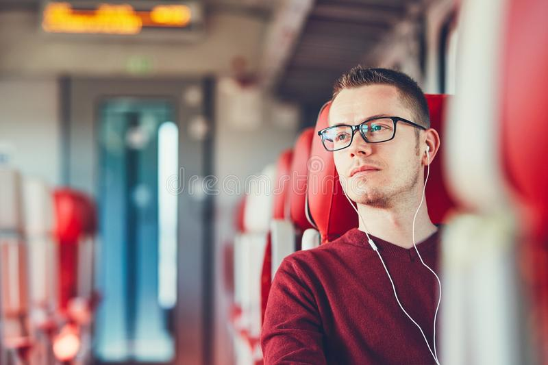 Young man traveling by train stock photos