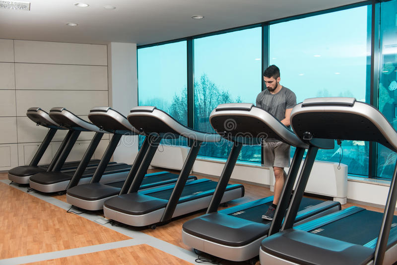 Young Man On Treadmill. Handsome Man Running On The Treadmill In Gym stock images