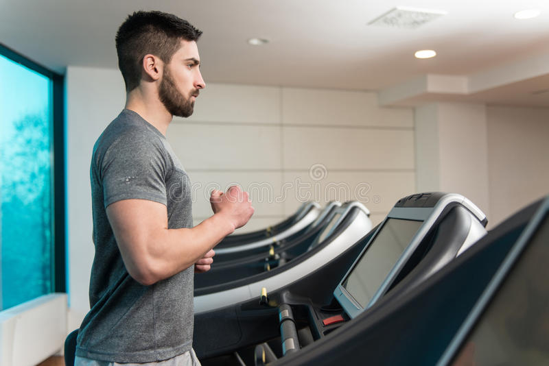 Young Man On Treadmill. Handsome Man Running On The Treadmill In Gym stock photography