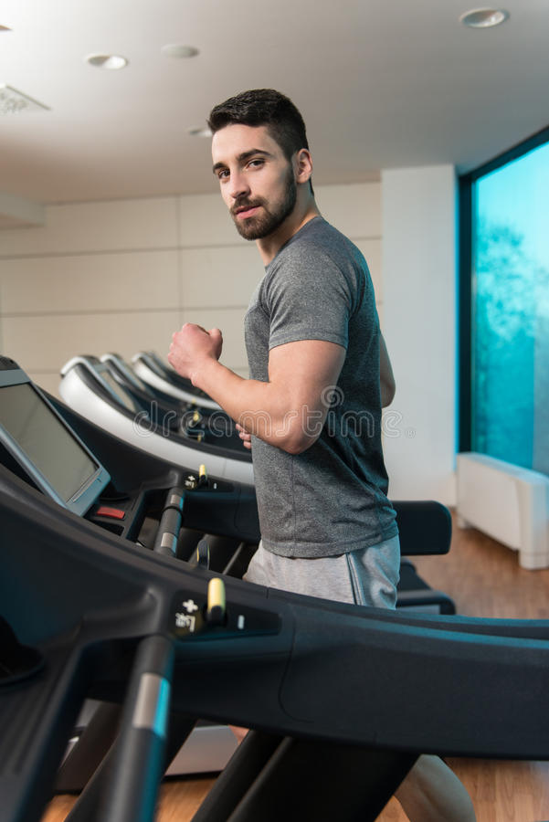 Young Man On Treadmill. Handsome Man Running On The Treadmill In Gym royalty free stock photo