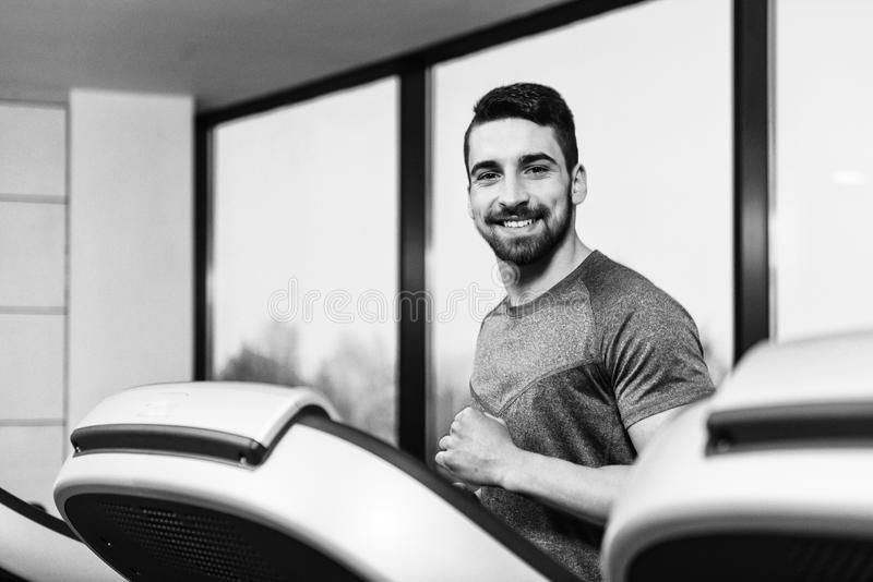 Young Man On Treadmill. Handsome Man Running On The Treadmill In Gym stock photo