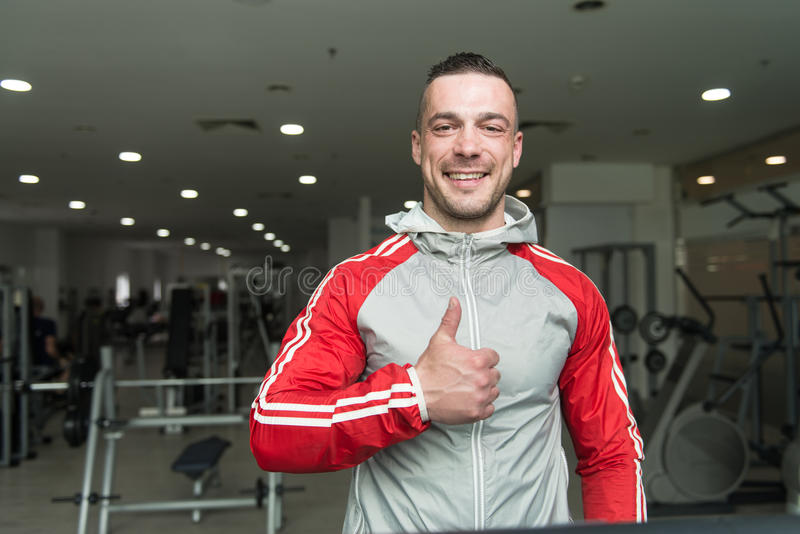 Young Man On Treadmill. Handsome Man Running On The Treadmill In Gym stock image