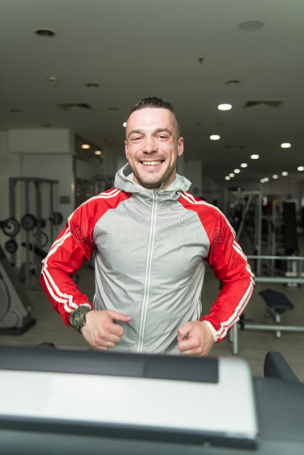 Young Man On Treadmill. Handsome Man Running On The Treadmill In Gym royalty free stock photos