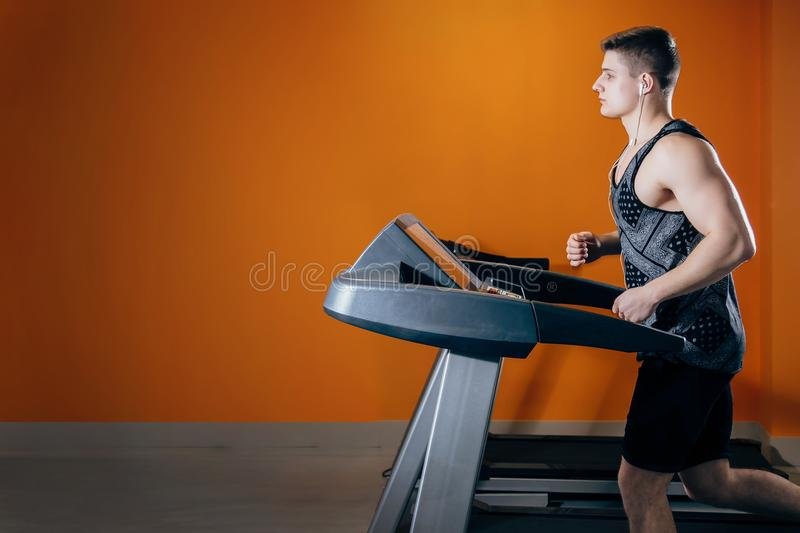 Young man on the treadmill royalty free stock images