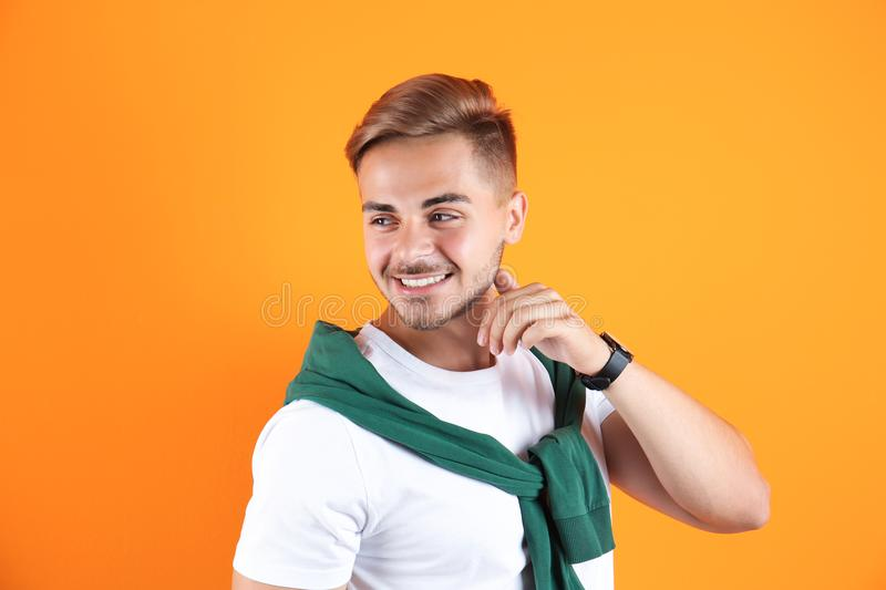 Young man with trendy hairstyle. On color background stock photography