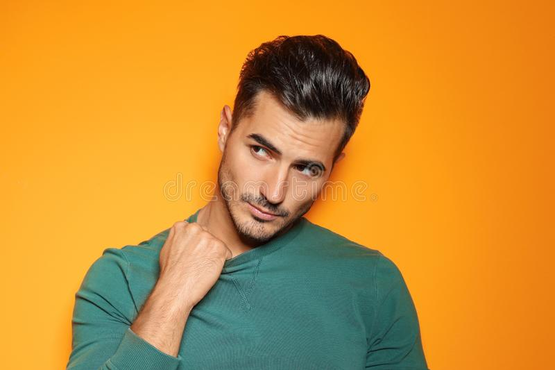 Young man with trendy hairstyle posing. On color background stock image