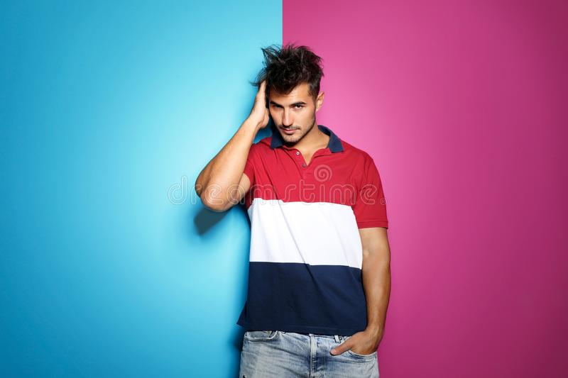 Young man with trendy hairstyle posing. On color background royalty free stock photography