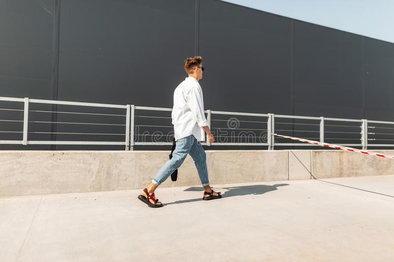 Young man with a trendy hairstyle in a white shirt in vintage blue jeans in leather sandals with a black bag walks down the street. Near a gray building. Modern stock photography