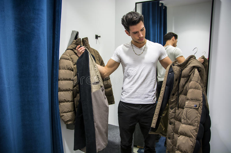 Young Man Trying on Clothes in Clothing Store. Young Handsome Man Trying on Clothes in Clothing Store's Changing Room in Front of a Mirror or in Room Closet stock photo
