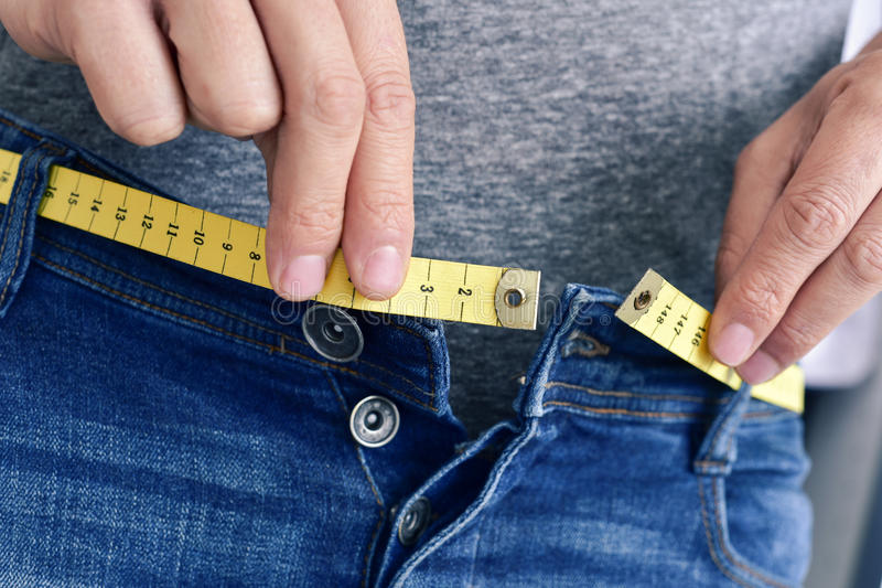 Young man trying to fasten his trousers. A young man with a measuring tape as a belt tries to fasten his trousers, because of the weight gain stock photo
