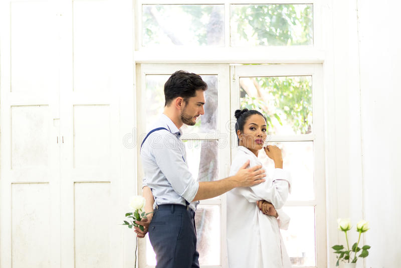 Young man trying to reconcile his girlfriend offering white rose. Young men trying to reconcile his girlfriend offering white rose in the white room royalty free stock images