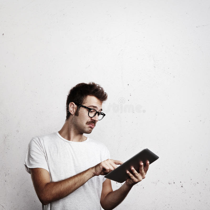 Young man trying to use digital tablet stock photography