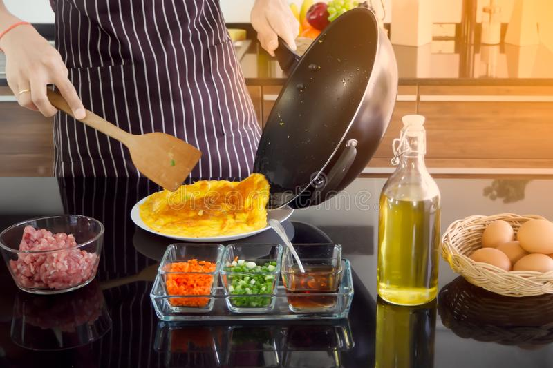 Young man turn pan and use wood spatula to flip omelette out onto the plate,making breakfast in the morning. New generation modern. Lifestyle concept stock photos
