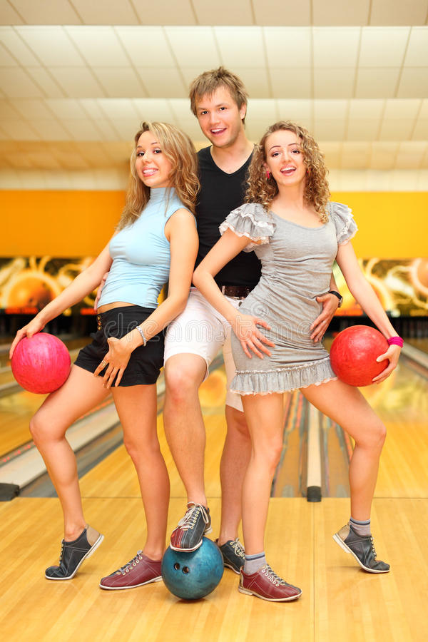 Download Young Man And Two Girls Hold Balls In Bowling Club Stock Image - Image: 25150465