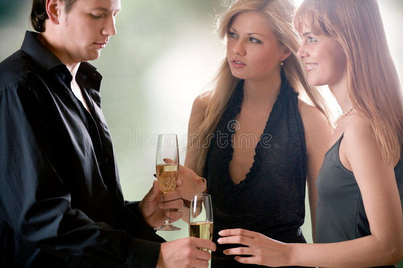 Young man with two glasses with champagne and two women standing royalty free stock image
