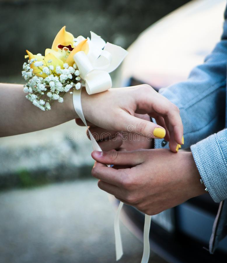 Young man tying bow, ribbon on the girls hand. Young man tying bow decorated by yellow and white flowers on the girls hand royalty free stock photo