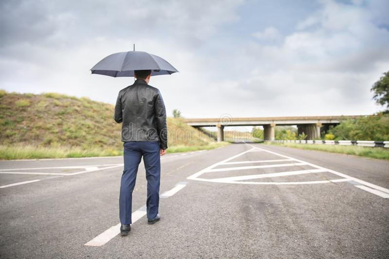 Young man with umbrella going along road. Concept of choice royalty free stock photo