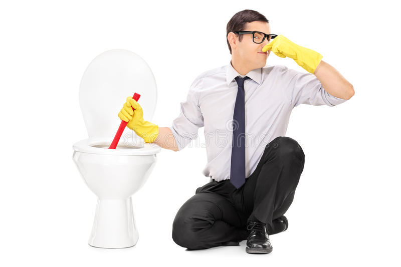 Young man unclogging a stinky toilet with plunger. Isolated on white background stock images