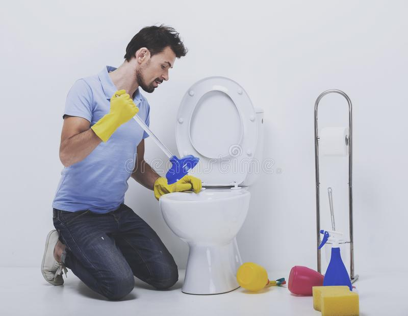 Young man unclogging toilet with plunger. Plumber sits next to wc royalty free stock photos